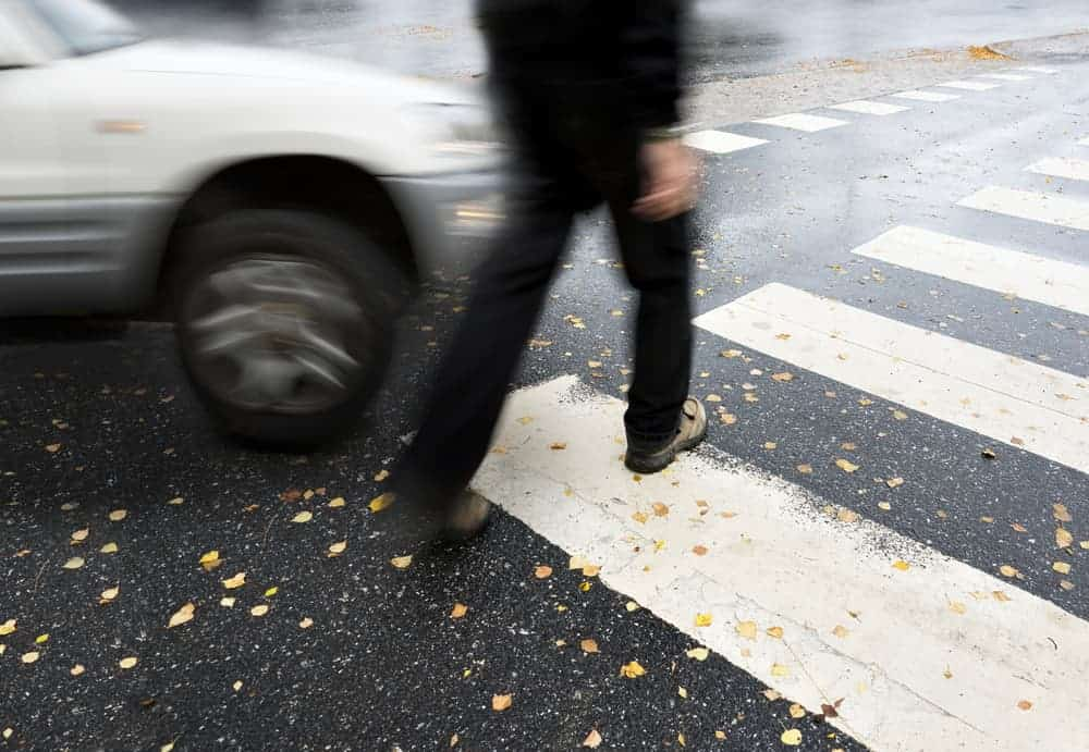 pedestrian crossing at cross walk with car coming through
